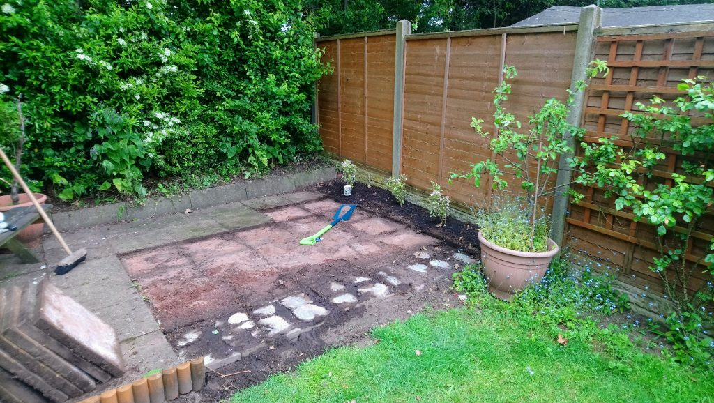 Patio area with some slabs lifted. Lumps of concrete showing through at the front.
