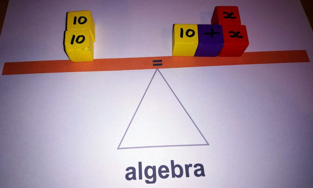 picture of a seesaw with algebraic formula represented with wooden blocks.